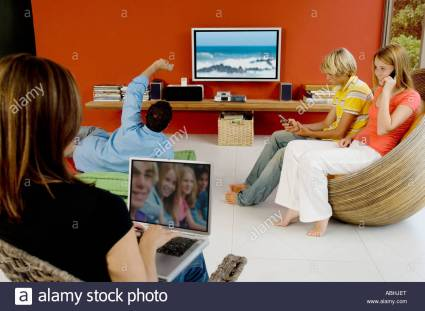 family-in-living-room-woman-using-laptop-man-watching-tv-2-teens-using-abhjet